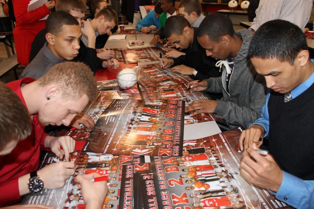 Members of the Hawks men's basketball team autograph the poster commemorating their 4th place finish in state this year. (Angelo Comeaux | HBN)
