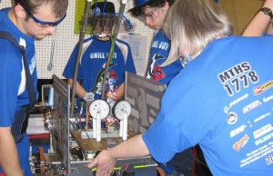 Members of the 2011 robotics team work to assemble their robot at the kickoff event.