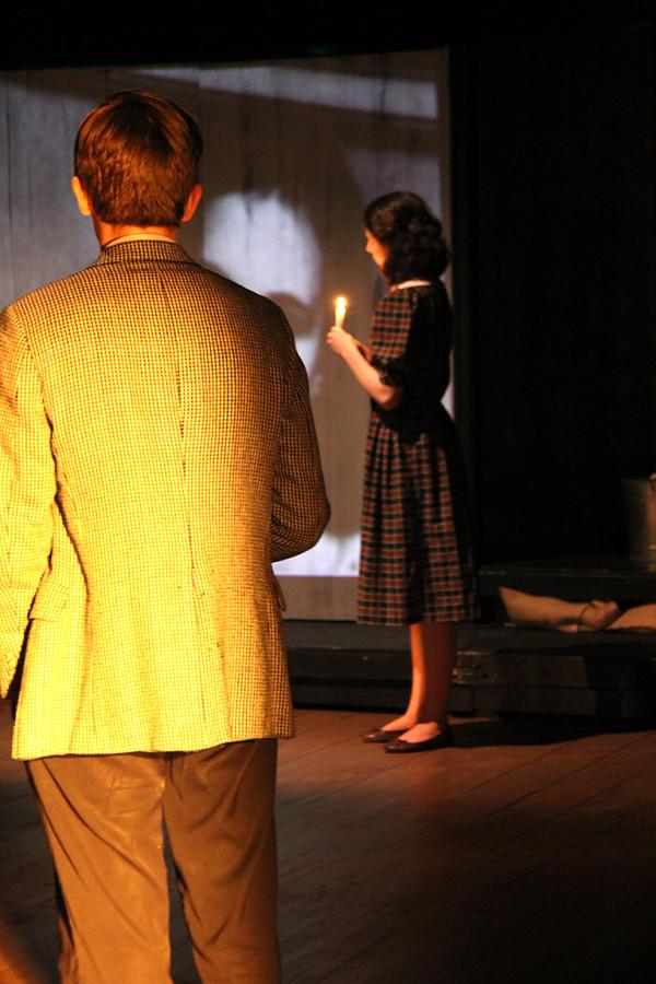 Haley Wiseman as Anne Frank and Tyler Grabarczyk as Heinz stand holding candles to honor the lives lost during the Holocaust.