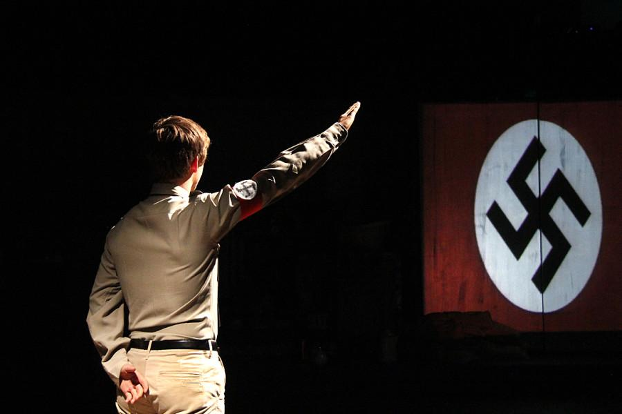 Taron Castleton as a Hitler Youth gives the Nazi Salute to the Nazi flag portrayed on screen.