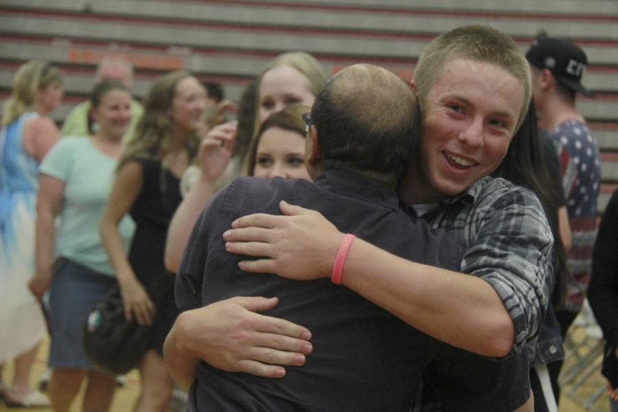 Senior Jaden Yackley hugs science teacher Jonathan Tong at the end of the Moving Up assembly.