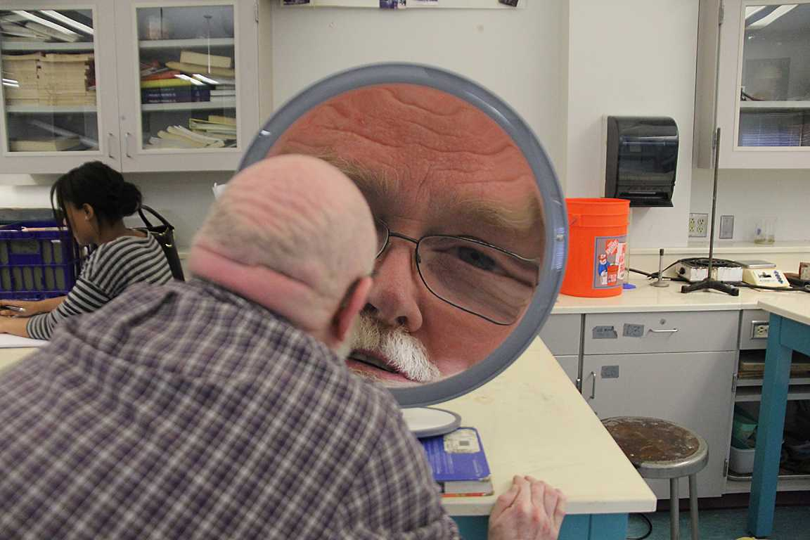 Science teacher Gil Comeau displays a physics lesson using an unusual mirror in hopes to make the students laugh.
