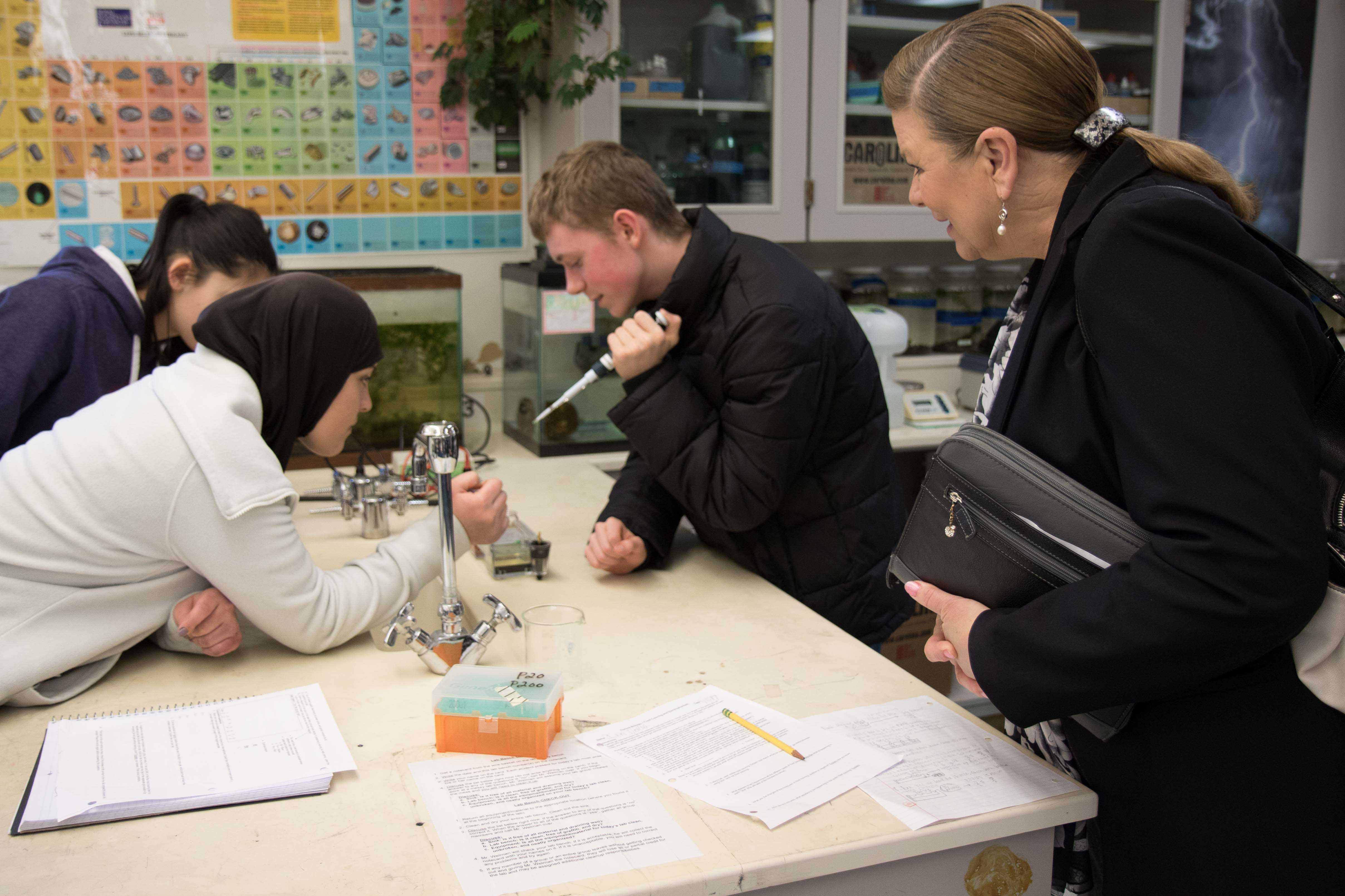 Superintendent+Kris+McDuffy+watching+intently+as+a+freshmen+sets+dyes+for+gel+electrophoresis.+