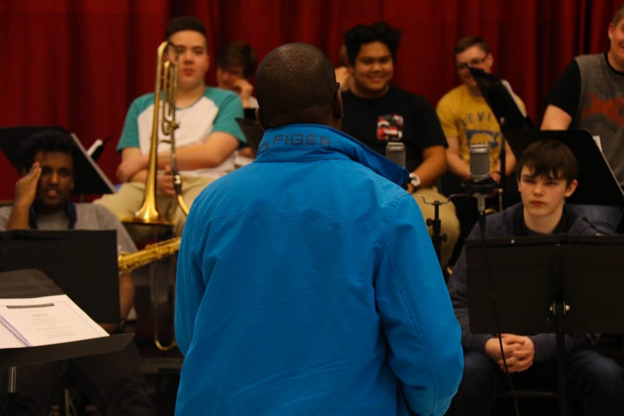 The band members watch with smiles on their faces as Williams demonstrates scale techniques to the band on his tenor saxophone.