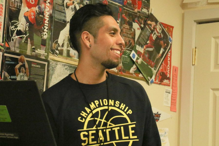 Aguiniga smiles at a student while they tell him a joke.