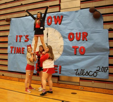 Cheerleaders pose in front of the main Wesco ASB Conference banner.