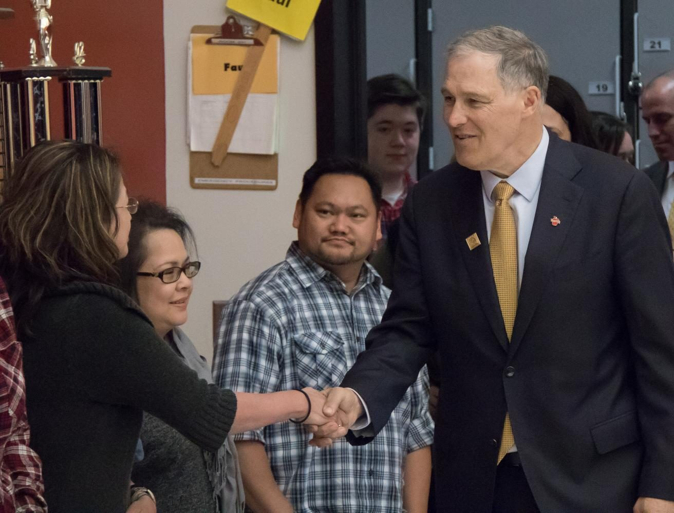 As he enters the band room, Governor Inslee shakes hands with parents of MTHS students.