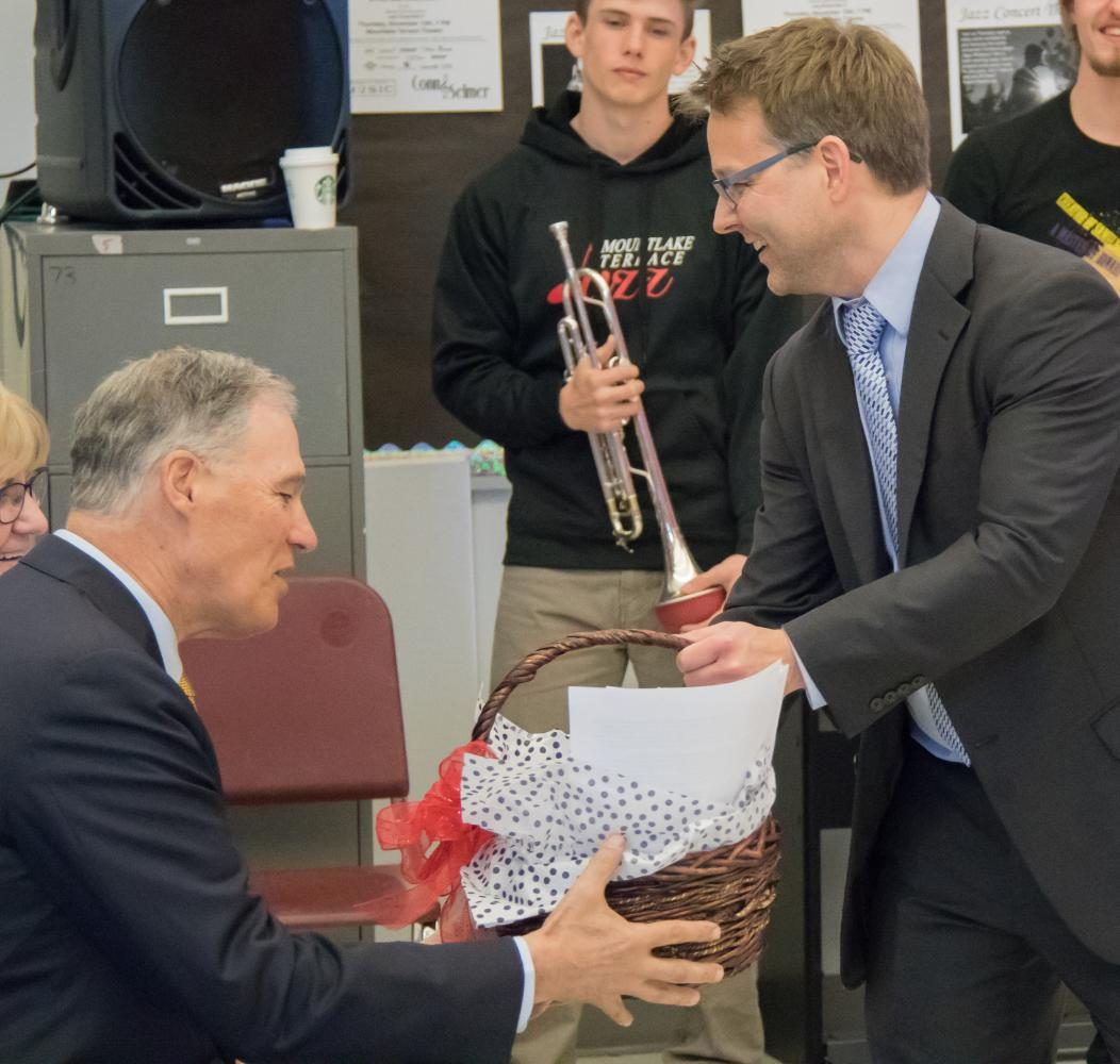 Band director Darin Faul gives Inslee a gift basket from the band program.