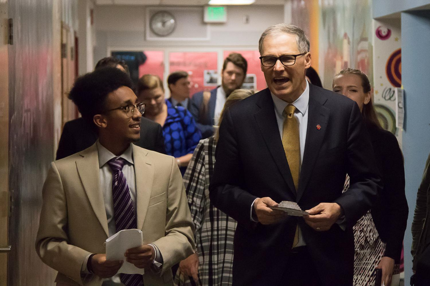 Abraham speaks with Washington state Governor Jay Inslee as he leads Inslee through the art hallway. Inslee's stops included STEM, music and journalism.