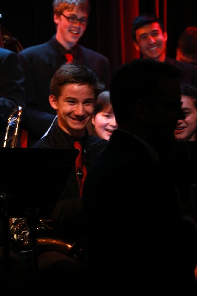 Sophomore Owen Moreland laughs with jazz 2 after joking with director Darin Faul about the meaning of the song