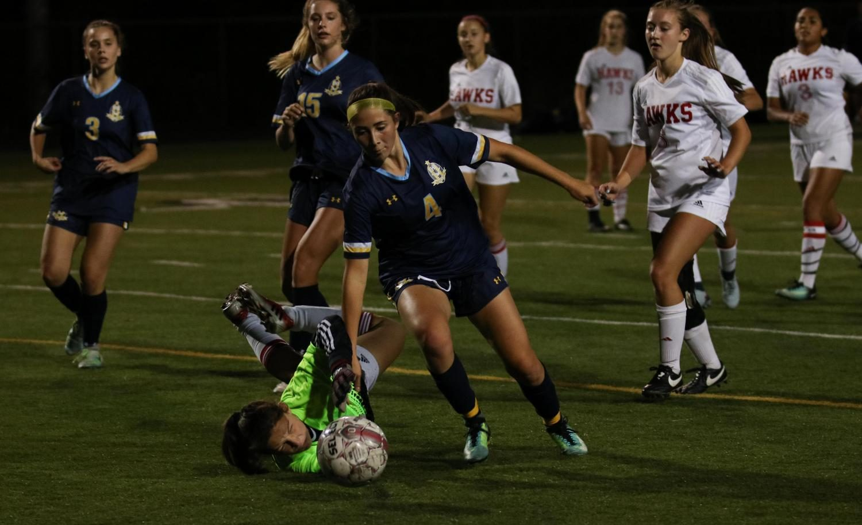 Goalie Maisey Knorr dives to prevent an Everett offender from scoring.