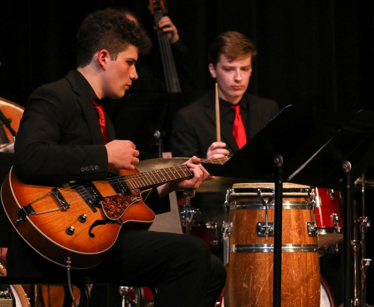 Senior Gian Neri strums along with the rhythm sections.