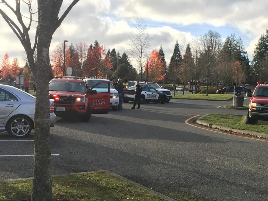Police and fire department vehicles park in the school lot.
