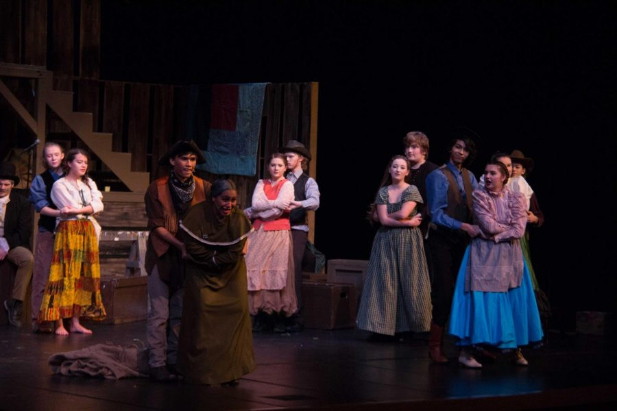 As Little Harp (Seth Timple) deceives the lusty Salome (Abbie Apana) to get in a sack, the entire ensemble watches eagerly as she goes to her doom.