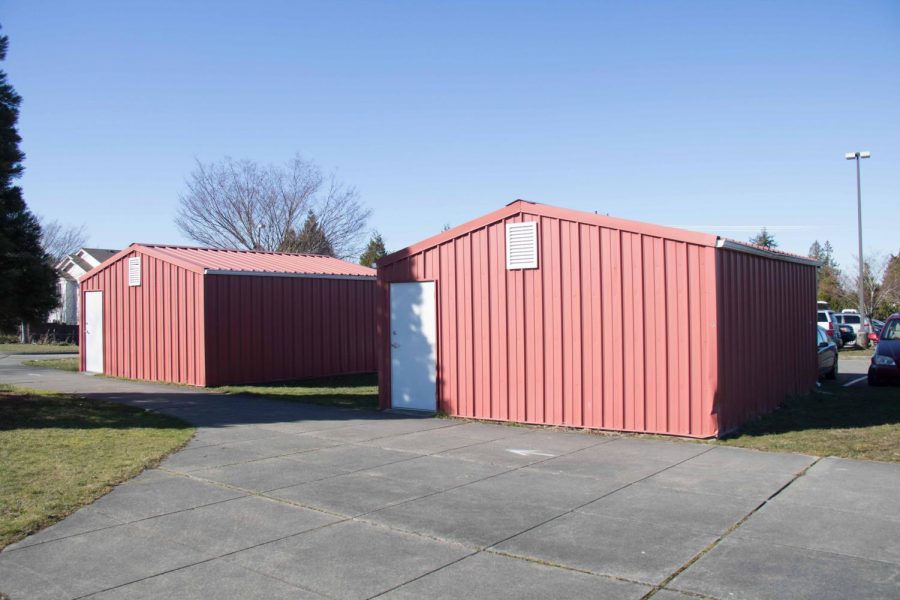 On a sunny day, the two sheds sit behind the school in between the greenhouse and the softball field.