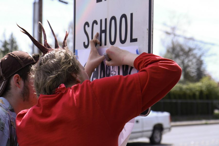 Senior Eli Longacre writes on a piece of paper that he tapped over a stop school zone sign, changing the message to say