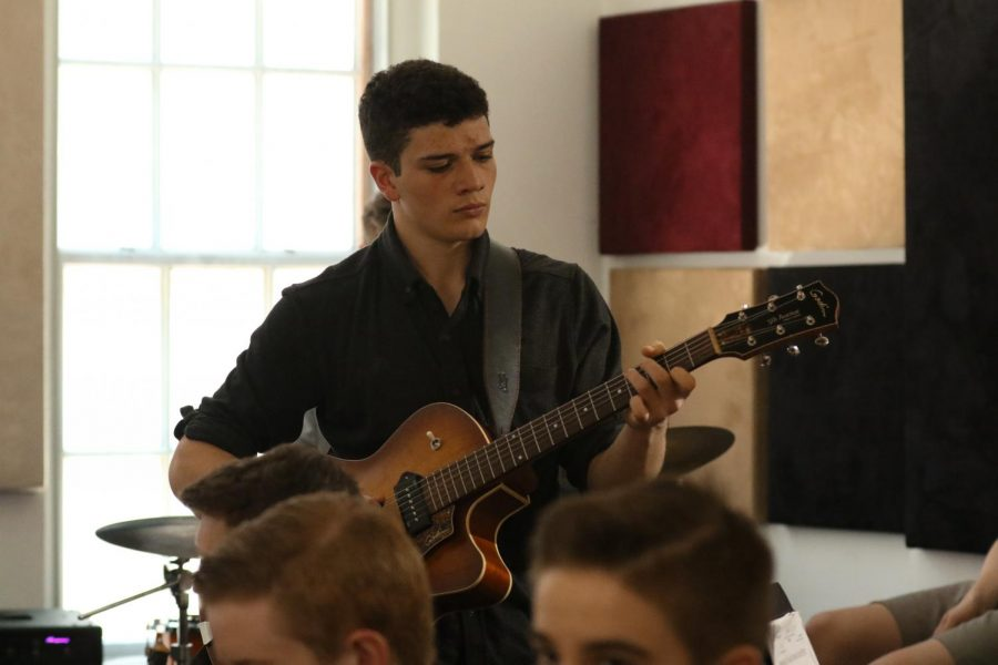 Senior Gian Neri stands for his guitar solo, which sparked a conversation between his music and DiCioccio, who asked for the rest of the story Neri has to tell throughout his solo.