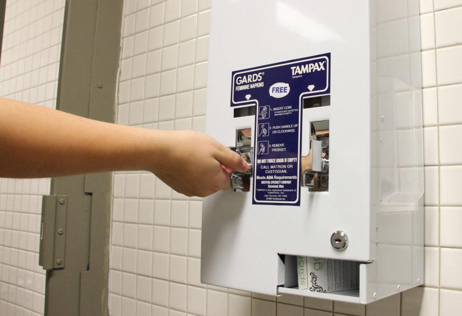 A student turns the knob on the left side of the menstrual hygiene product dispenser, causing a sanitary pad to come out. The machine exclusively offers one brand of pads and tampons, but is able to distribute these products for free.