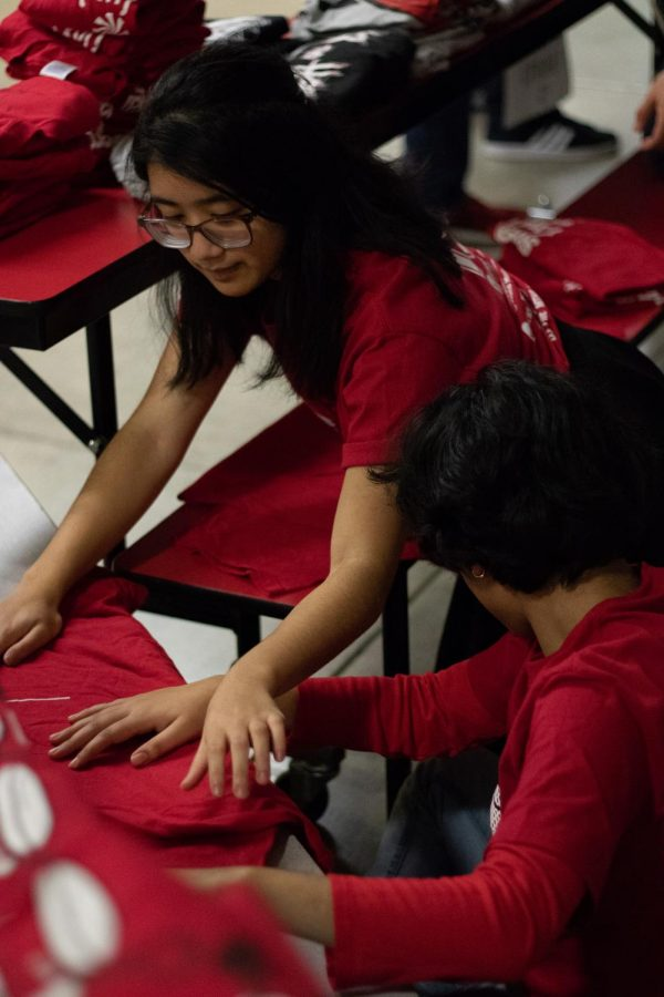 Senior Marianne Nacananay and freshman Ratika Khanal prepare shirts to sell during the event.