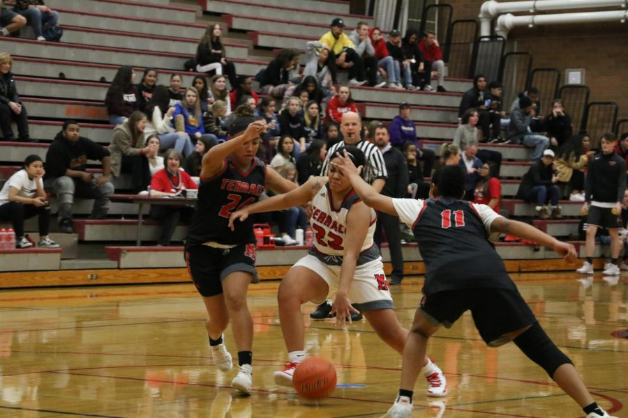 Trinity Prout, a senior, attempts to take possession of the ball, but is blocked by Kierra Scott and Lydia Prelow.