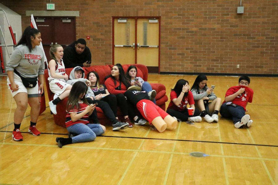 Students who were selected from the crowd watch a quarter of the game court side on a couch.