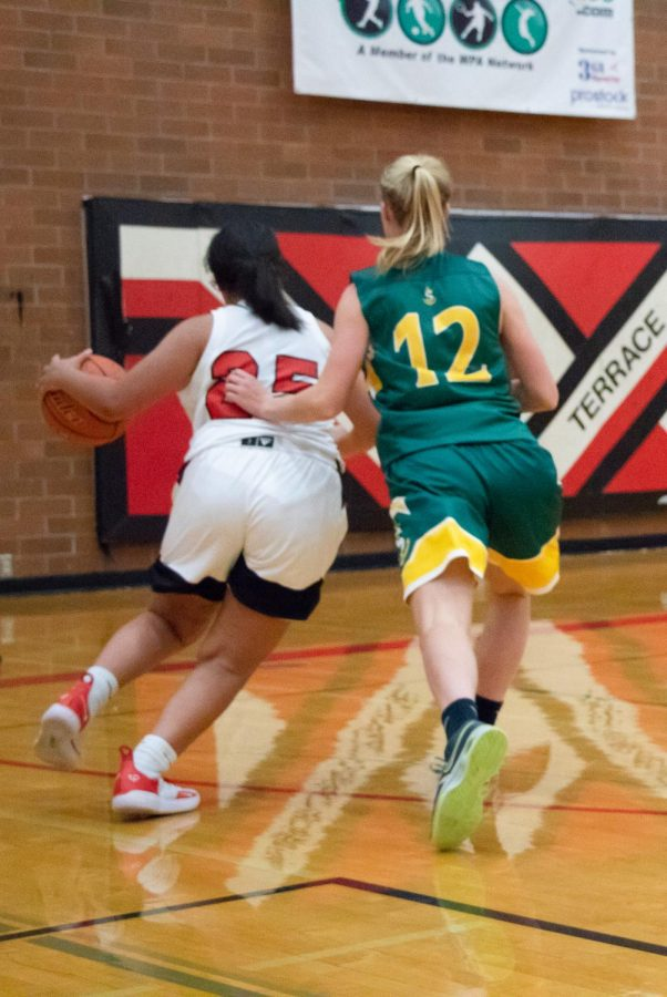 Senior guard Trinity Prout drives to the basket pass Sehome's Payton Boehm.