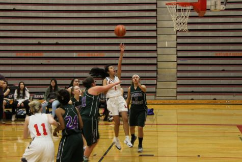 Freshmen Gwyneth Camacho attempts a layup threw two Woodway defenders`