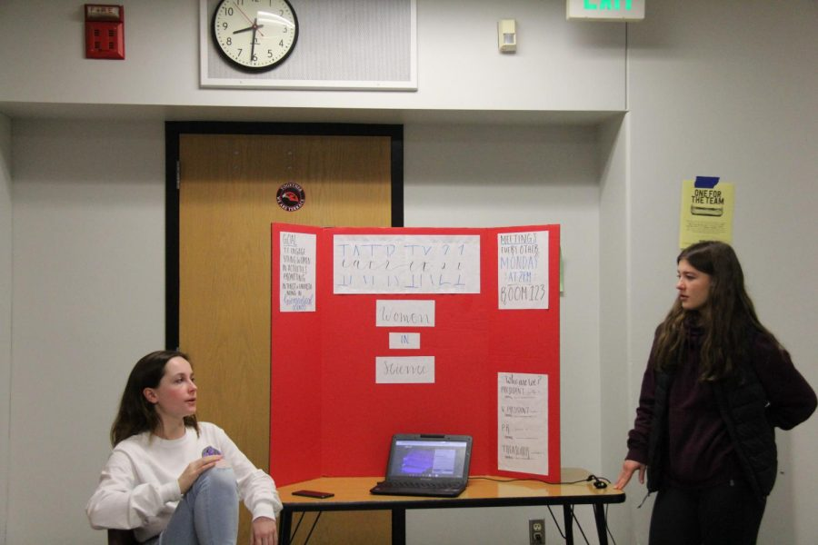 Seniors Sally Benedict and Kaylee Hynek at their board for IATRIX21, a club focused on women in science.