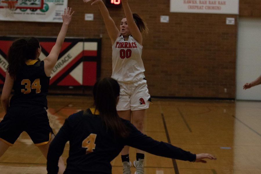 Sophomore Berit Simonsen Taking a three-point shot being guarded by senior Yuni Septimo-Ruiz.
