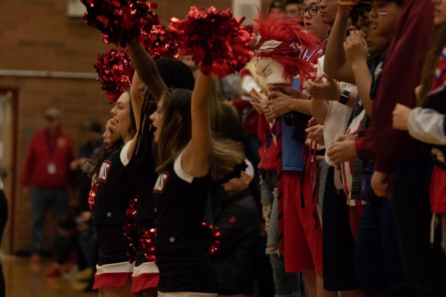 The MTHS Cheerleaders raise their pompoms as the players dribble down the court.