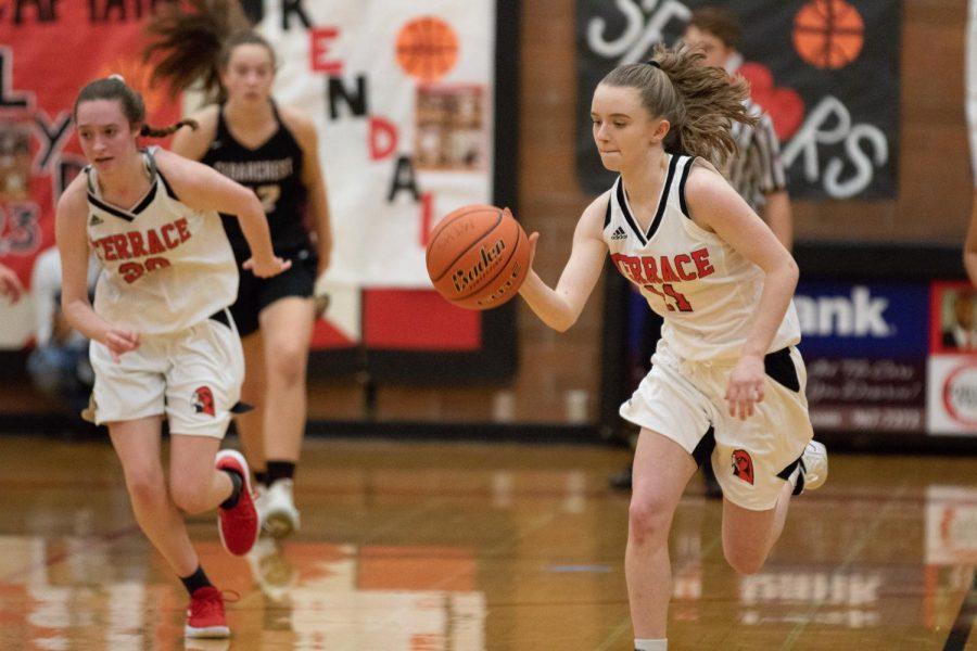 Senior Kendall Glenham dribbles the ball across the court.