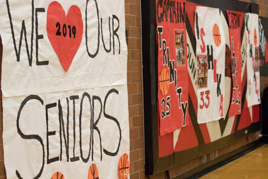 The team decorates one side of the gym with posters for Senior Night, the final home game of the season celebrating the seniors.