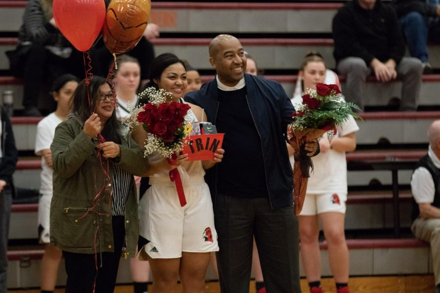 The Prout family smiles as the crowd cheers them on. Each senior receives a bouquet of flowers with a basket of goods in celebration of her senior night.