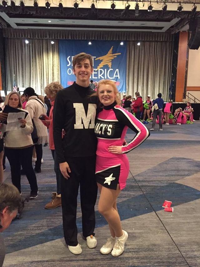 Senior Britta Sinclair poses for a photo with a fellow cheerleader.