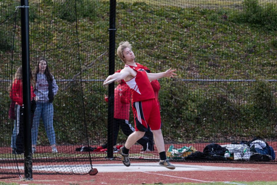 Senior Thaddeus Merten throws the discus, later winning the individual men's event.