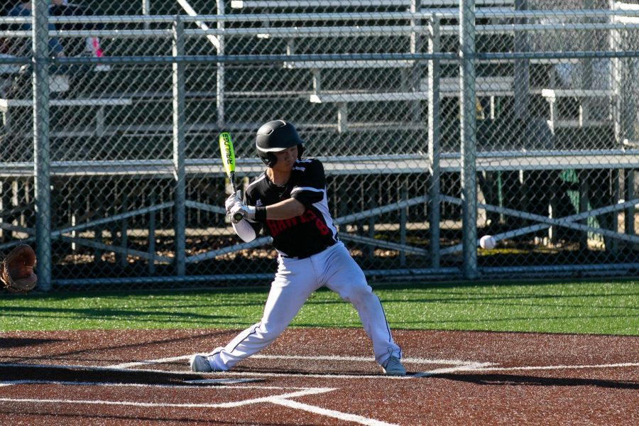 Senior Jonathan Kumai swings his bat at the ball