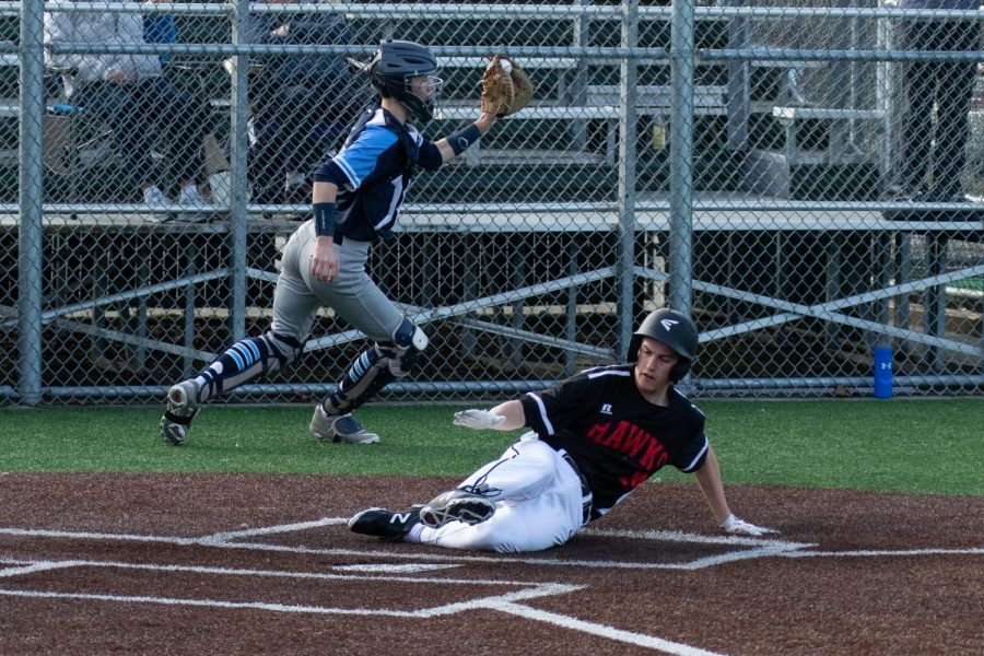 Sophomore Caden Alley slides home in the game vs Interlake