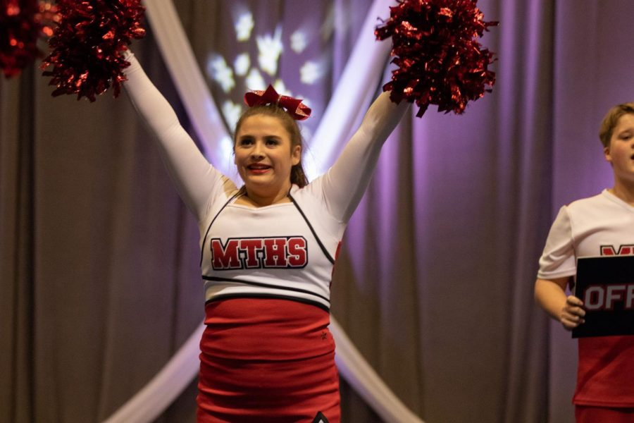 Lexi Daly, a junior, stands in a high v.