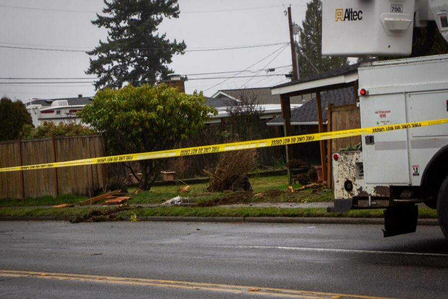 Snohomish PUD works on the site of the crash while the remains of the fence surrounding the damaged house are blocked off.