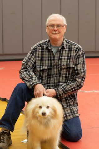 Former wrestler and Terrace alumnus Norm Buntting kneels on the wrestling mats in the Terraceum with his service dog Charlie. The pair are a common sight at wrestling matches, cheering on the current generation of competitors.