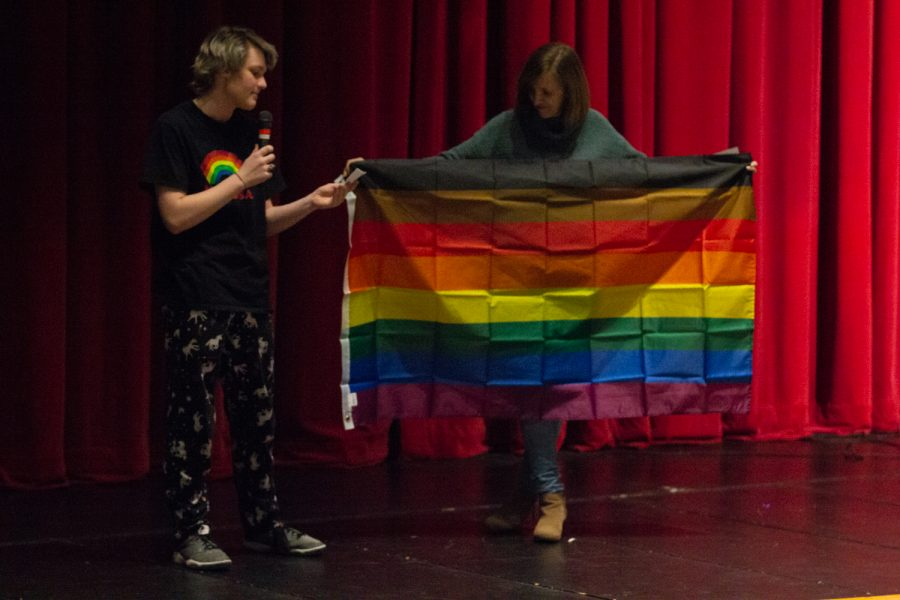 Sam Dilling, a sophomore, holds a rainbow flag which represents