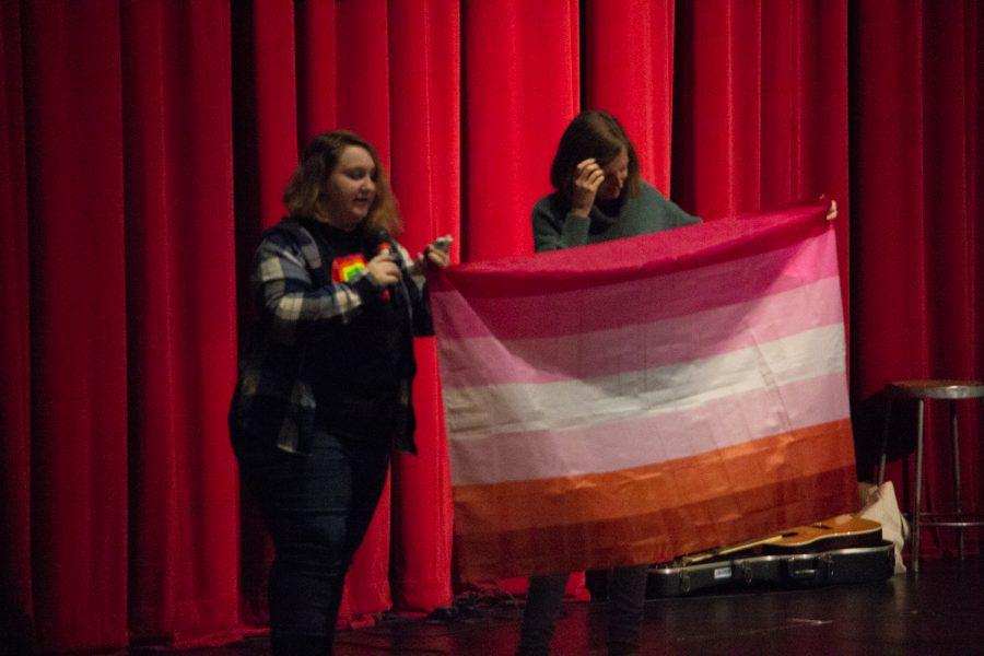 Kaylee Gohl, a senior, elaborates on lesbian pride history while the MTHS GSA advisor, Jennifer Widrig-Hodges, shows the flag.