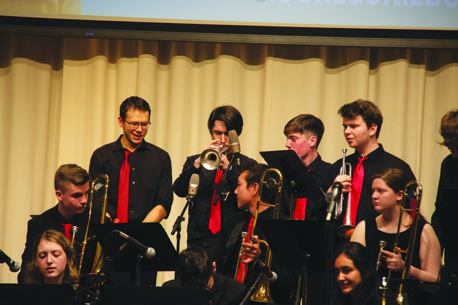 The MTHS Jazz 1 brass section looks on as senior Solomon Plourd plays a thick, blues-laden solo during the final concert of the University of Oregon Jazz Festival.