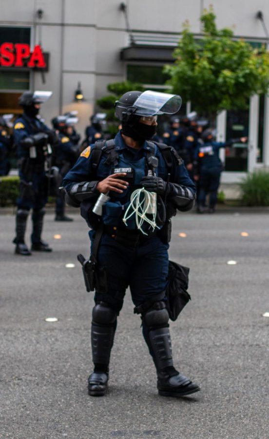 A Washington State Patrol trooper patrols the street.