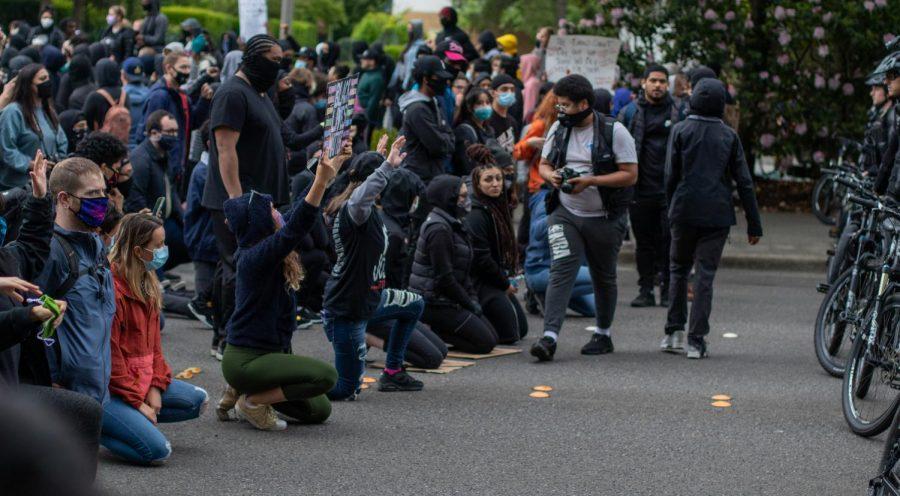 Peaceful protestors kneel in front of Bellevue PD.